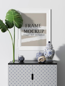 White wall frame mockup with ceramic vases and plant in scene