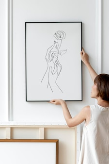 Japandi 장식 방의 벽에 프레임 모형 psd를 배열하는 여자