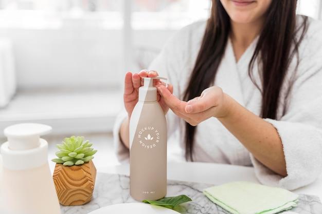 Женщина дома, используя увлажняющий крем