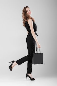 Woman in black with shopping bag.