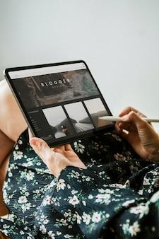 デジタルタブレットのモックアップでブログを書いている女性