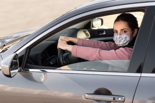 Woman in car wearing medical mask