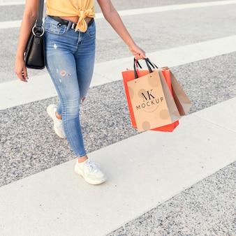 길을 건너와 모형 쇼핑 가방을 들고 여자