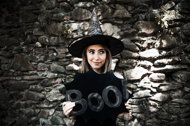 Woman dressed as a witch looking away and holding a boo! sign