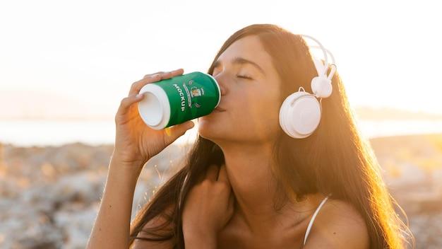 Женщина пьет из банки содовой и слушает музыку в наушниках