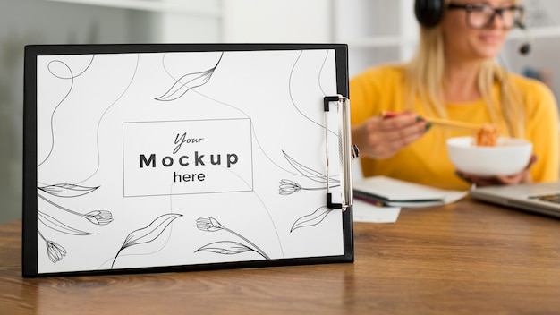 Woman eating at desk with clipboard mock-up