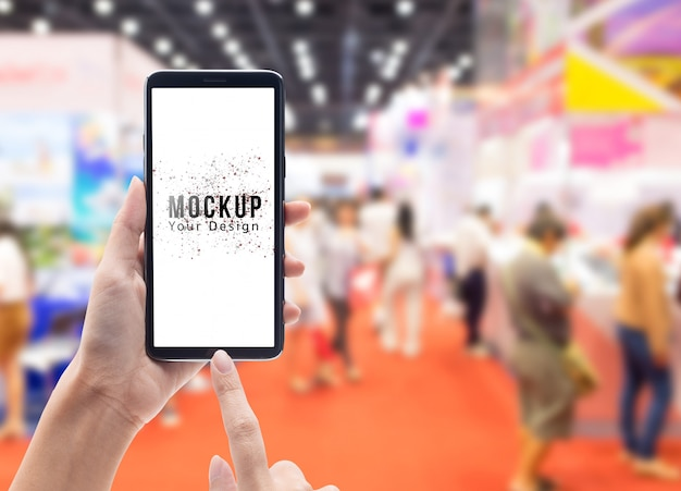 Женщина рука держа и трогательно черный смартфон с макетом пустой экран