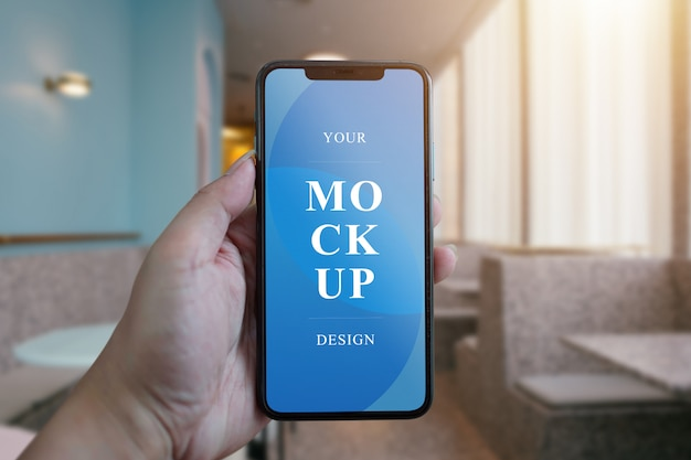 A woman hand holding phone device mockup in the cafe background.