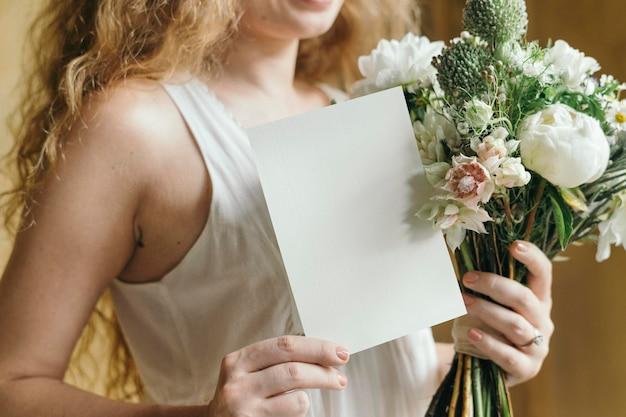 カードのモックアップと白い花の花束を保持している女性