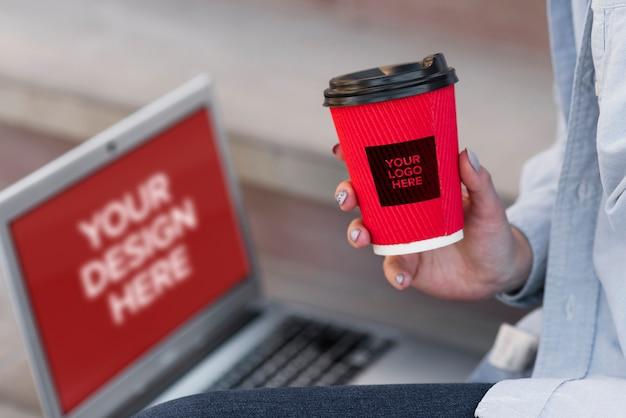 Женщина держит чашку кофе, сидя рядом с ноутбуком макет