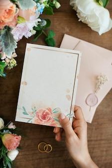 花のカードのモックアップを保持している女性