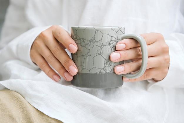 日本のパターンのコーヒーカップpsdモックアップ、リミックスを保持している女性