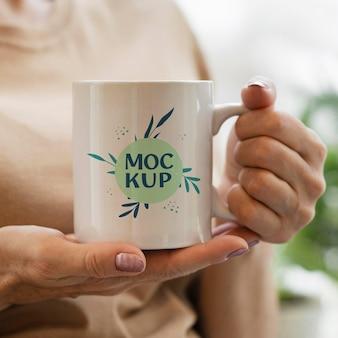 彼女の都会の果樹園でモックアップマグカップを保持している女性