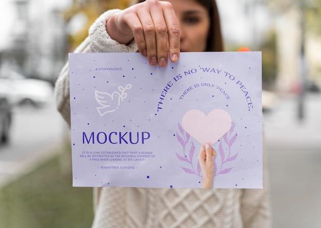 非暴力デーのモックアップ紙を持っている女性