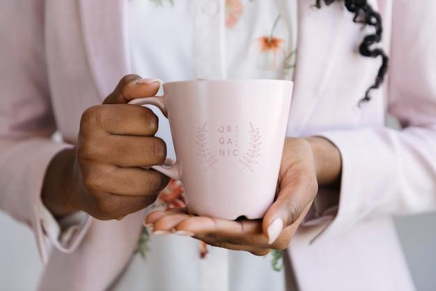 ピンクのマグカップのモックアップイラストを保持している女性