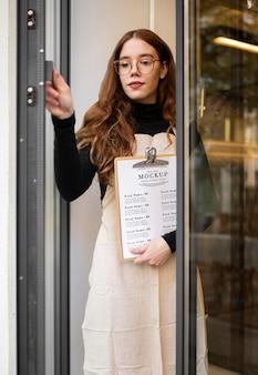 レストランメニューのモックアップを保持している女性