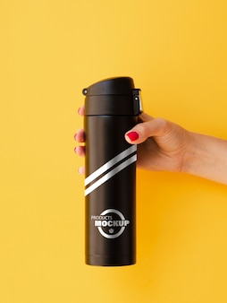 Woman holding a black thermos mock-up on yellow background