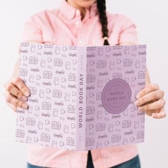 Женщина, держащая макет обложки книги Бесплатные Psd