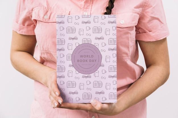 Женщина, держащая макет обложки книги Premium Psd
