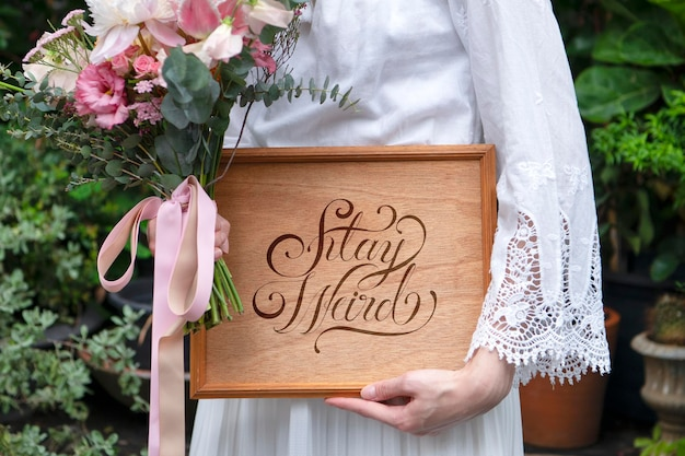 Woman holding a bouquet of flowers with a wooden board