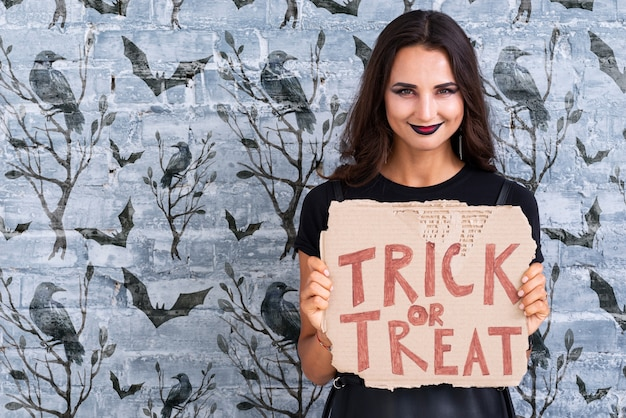 Woman holding a card with trick or treat lettering