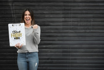 Woman holding clipboard mockup with black friday concept