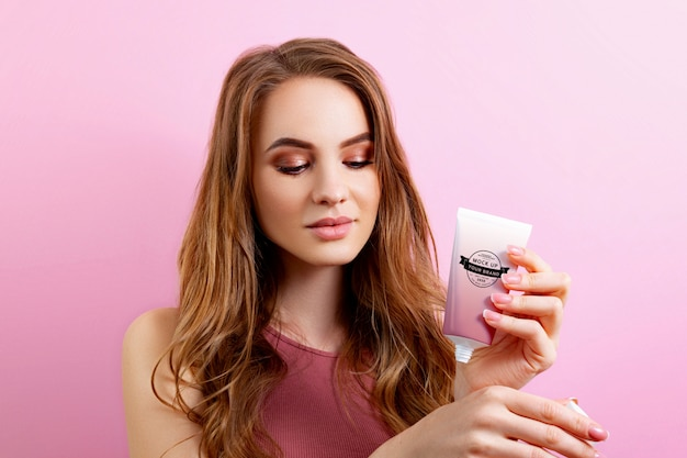 Woman holding cream tube mockup