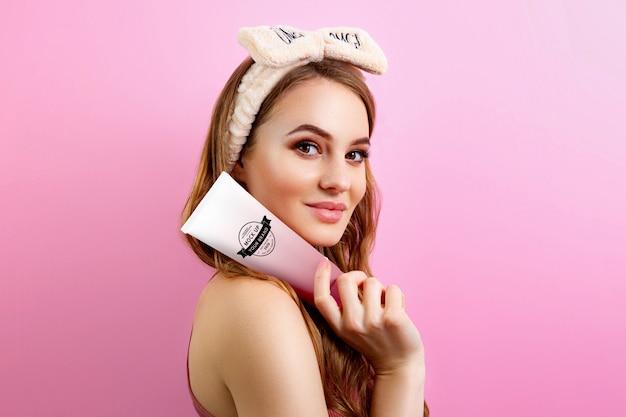 Woman holding cream tube mockup