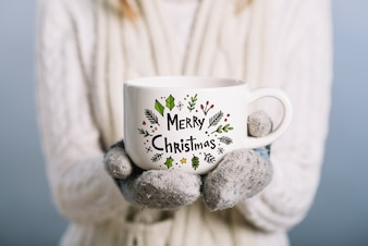 Woman holding cup mockup with christmas concept