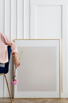 Woman holding a flower sitting by a frame