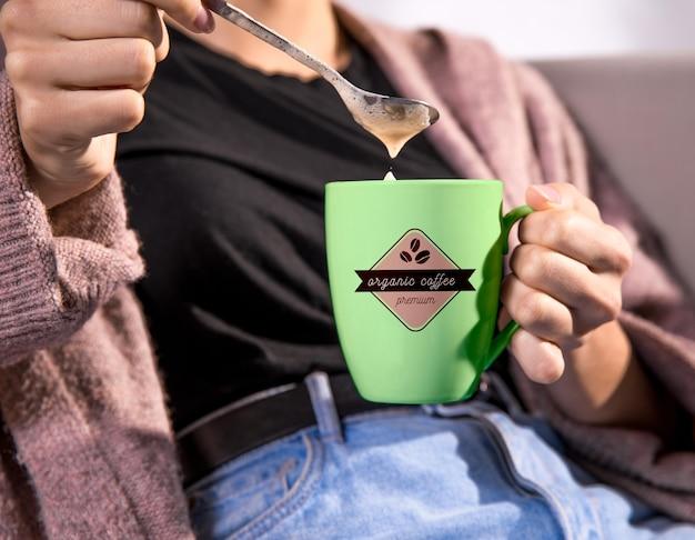 緑のコーヒー・マグを保持している女性
