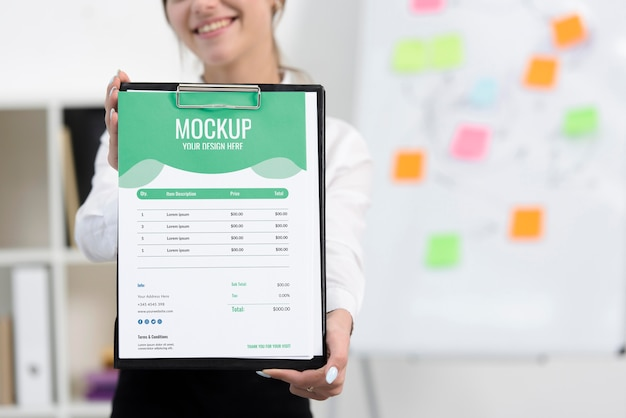 Woman holding a green mock-up clipboard