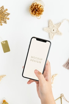 Donna che mantiene il suo telefono sopra il mockup di ornamenti natalizi in oro