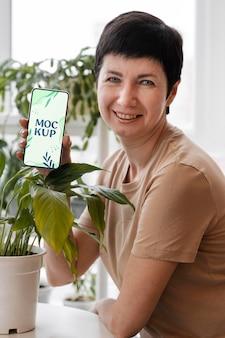 Donna con in mano un modello di smartphone nel suo frutteto urbano