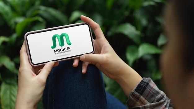 Woman holding mockup smartphone