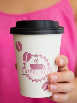 Woman holding paper coffee cup mock-up