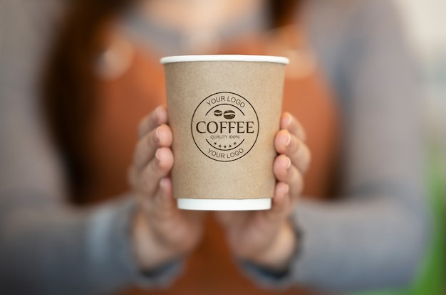 Woman holding paper coffee cup mockup