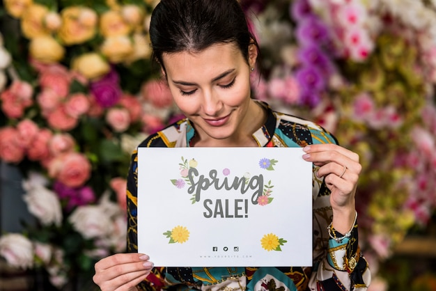 Woman holding paper mockup for spring sale