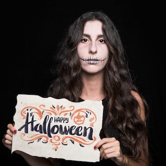 Woman holding paper with halloween lettering