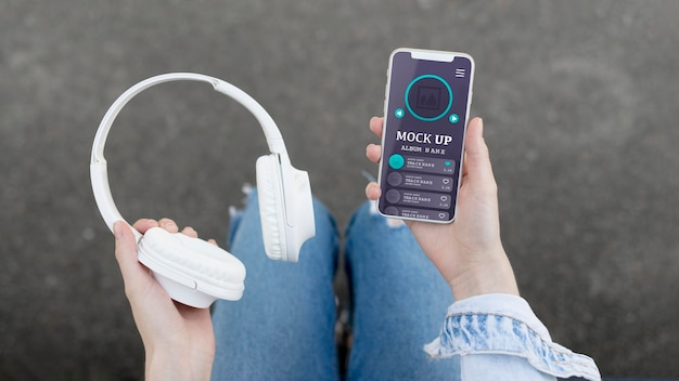 Woman holding phone with music app mock-up and headphones