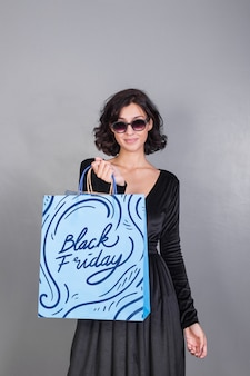 Woman holding shopping bag mockup with black friday concept