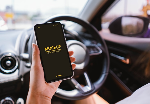 Woman holding smartphone mockup in the car