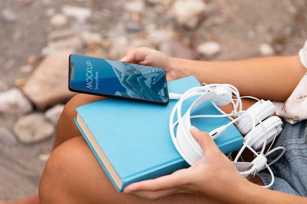 Donna che tiene smartphone con libro e cuffie