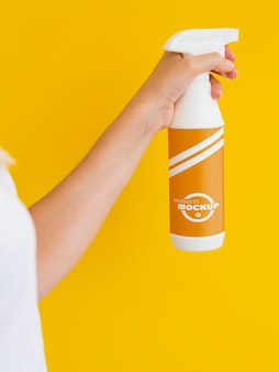Woman holding a spraying bottle mock-up