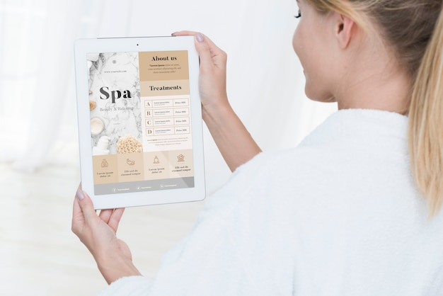 Woman holding tablet mock-up with spa offers