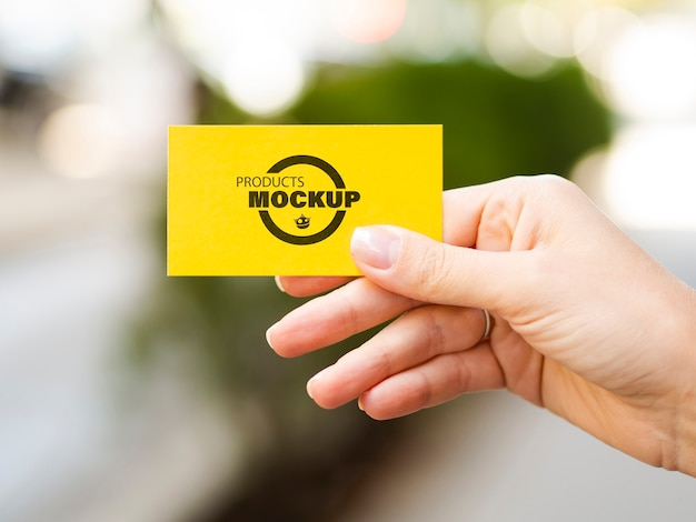 Woman holding up a yellow business card