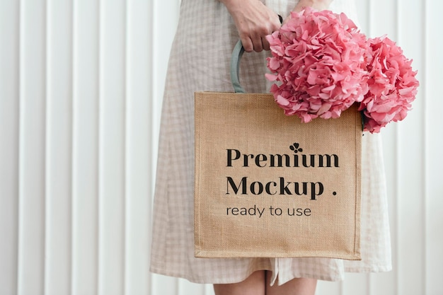 Woman holding a woven tote bag mockup with pink hydrangea flowers