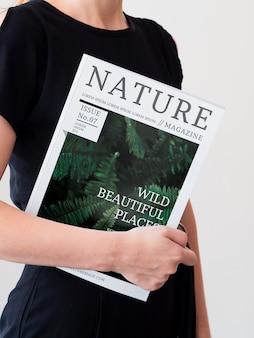 Женщина в черном платье держит журнал макет