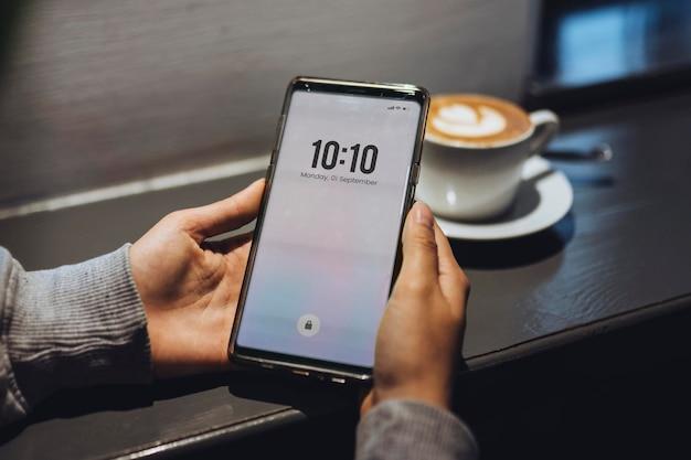 Женщина в кафе с помощью мобильного телефона