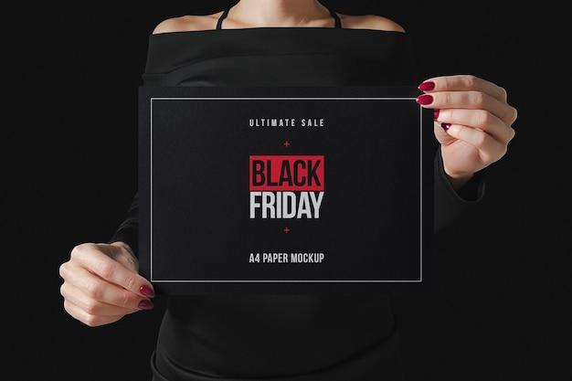Женщина в черном, держащая бумажный макет